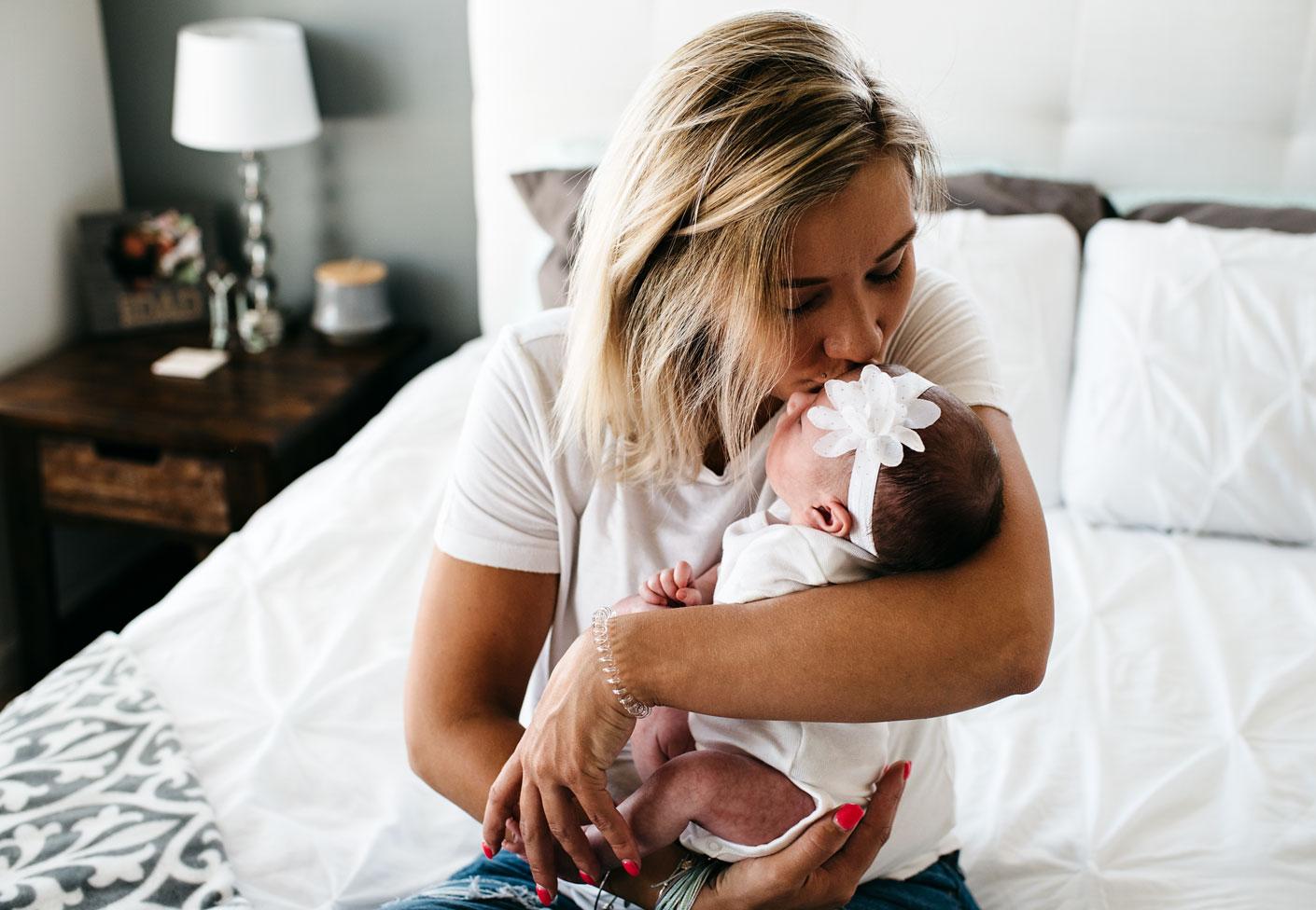 Mom kissing newborn